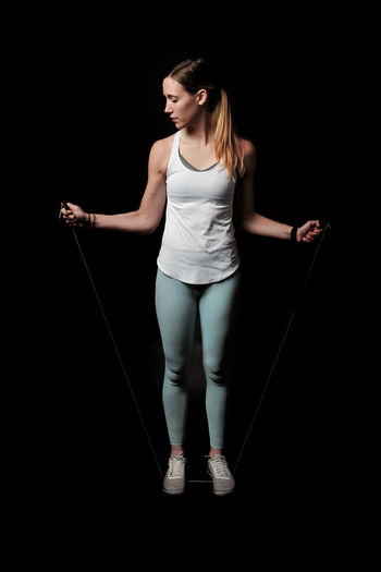 Young woman looking away while standing against black background Adult Sport Activity Athletic Attractive Beautiful Body Exercise Female Fit Fitness Girl Gym Health Healthy Lifestyle Muscle One person Pilates Pose Slim Sportswear Studio Training Weight Wellness Woman Workout Young Studio Shot Full Length One Person Black Background Indoors  Standing Young Adult Sports Clothing Front View Women Holding Casual Clothing Healthy Lifestyle Beautiful Woman Young Women Hairstyle