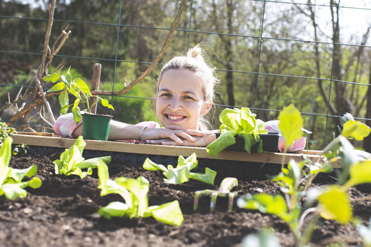 Smiling woman leaning on raised bed in yard