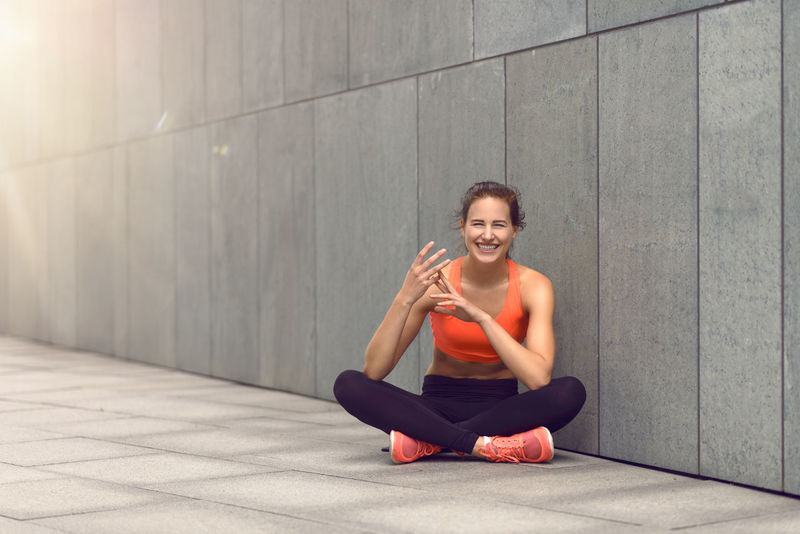 Cute woman counting with fingers while seated Athletic City City Life Counting Counting Cute Fingers Full Length Happy Healthy Lifestyle Laughing Motivation Outdoors Portrait Sitting Sports Training Urban Woman