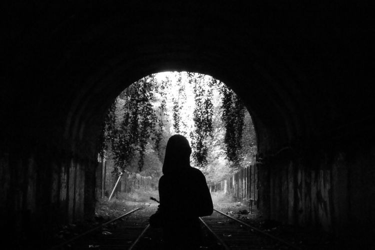 Silhouette of man in tunnel
