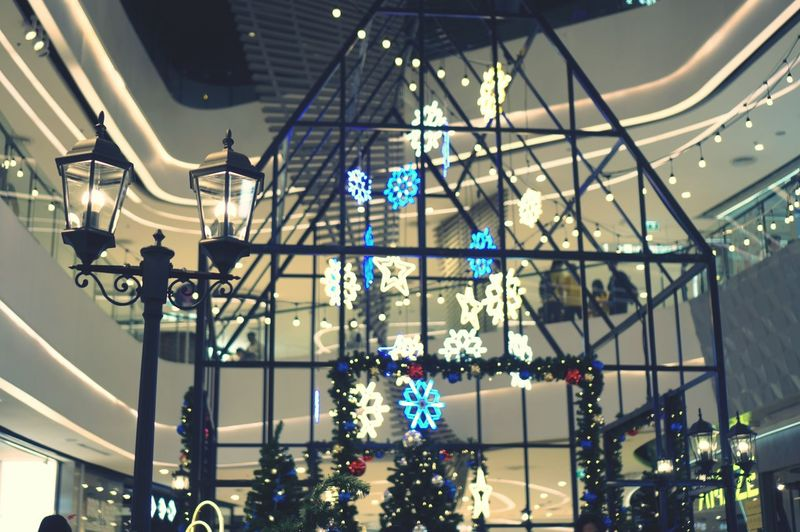 Low angle view of illuminated lights hanging from ceiling in shopping mall