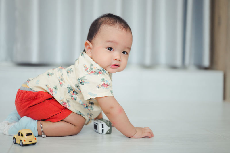 Portrait of cute baby boy playing with toy while sitting on floor at home