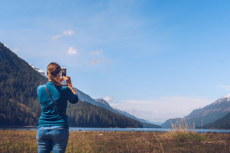 Full Length Of Woman Photographing Landscape Against Sky