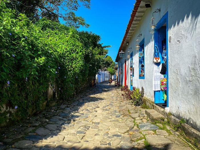 Footpath amidst buildings against blue sky