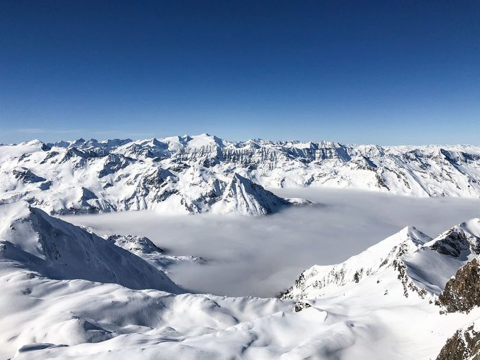 sunny day over clouds Winter Cold Temperature Snow Mountain Scenics - Nature Beauty In Nature Sky Tranquil Scene Snowcapped Mountain Tranquility Blue Copy Space Clear Sky Nature Mountain Range No People Non-urban Scene Environment Day Mountain Peak Kitzsteinhorn
