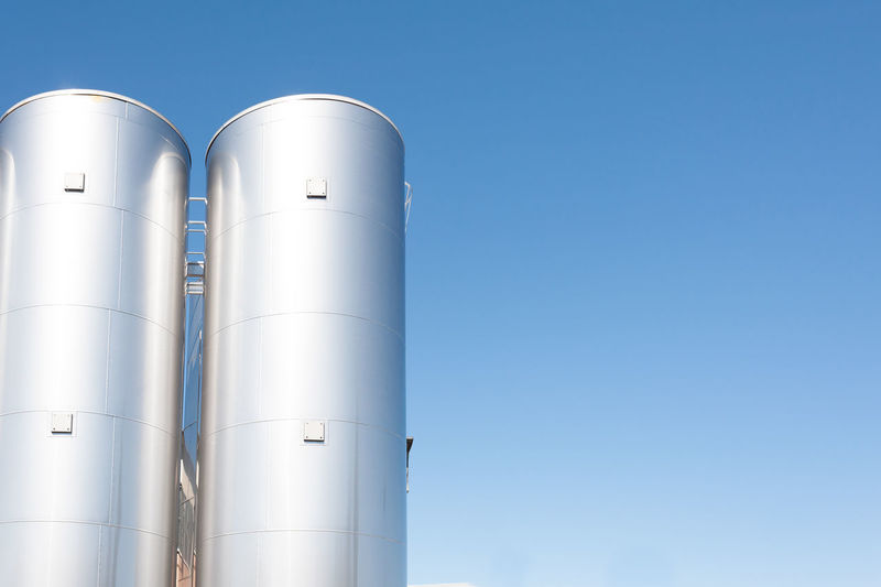 Industrial silos for chemical production, by stainless steel Blue Building Exterior Chemical Clear Sky Compartment Factory Industry Metal No People Outdoors Plant Refinery Silo Silouette & Sky Sky Stainless Steel Storage Tank White Color