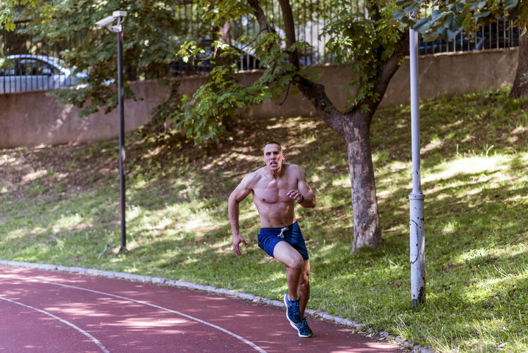 Shirtless muscular athlete running on sports track