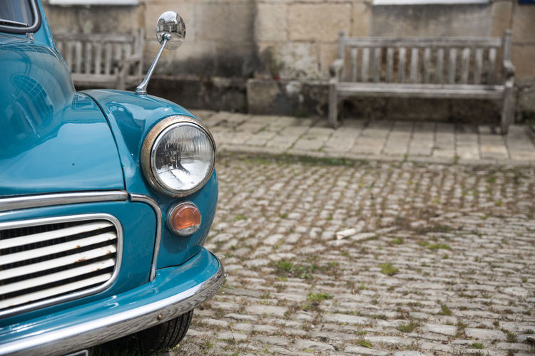 A classic car, vintage morris minor van in old fashioned surroundings like italy, britain, or cuba