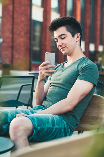 Smiling teenage boy using mobile phone in city
