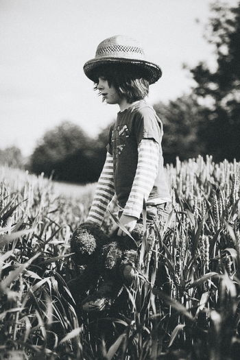 Boy holding teddy bear walking amidst wheat field against sky