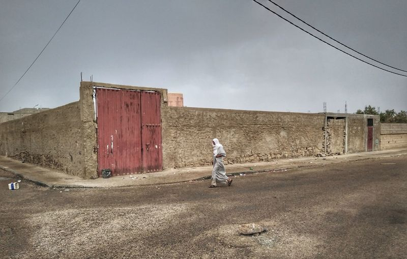 Side view of woman walking on road against sky