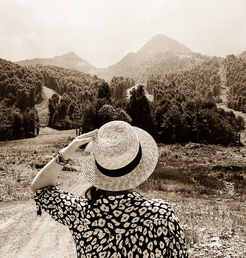 Rear view of woman holding onto straw hat looking at mountains