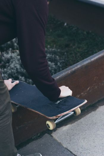 Midsection of man holding skateboard