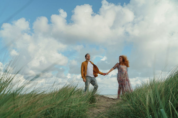 Couple standing on grass against sky