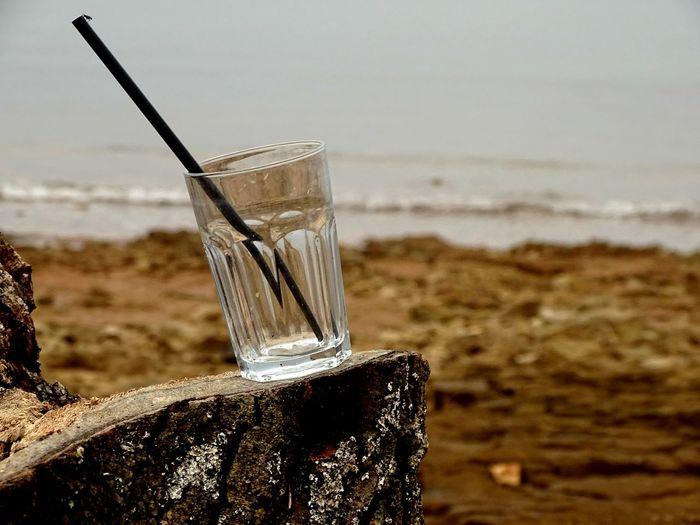 Close-up of glass of water on beach