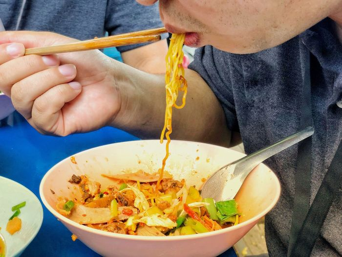 Midsection of man eating noodles with chopsticks