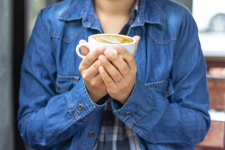 woman wearing blue jean shirt and hand holding a cup of flat white coffee Midsection Holding One Person Front View Focus On Foreground Real People Casual Clothing Lifestyles Cup Denim Food And Drink Button Down Shirt Indoors  Adult Day Blue Men Drink Standing Jeans