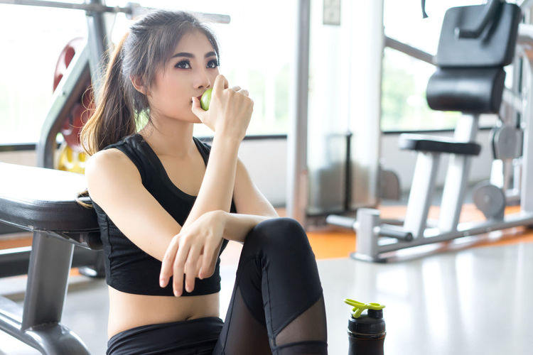 Young woman eating apple while sitting in gym