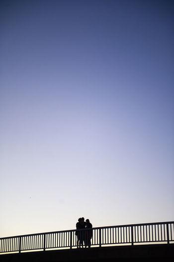 Silhouette woman walking on bridge against clear blue sky