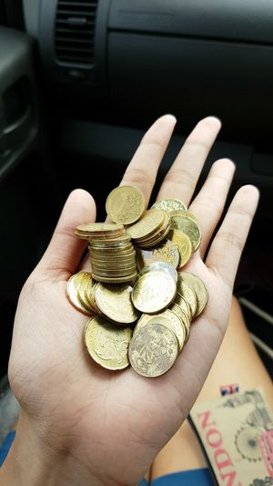 High angle view of cropped hand showing various coins in car