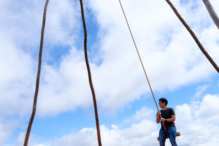 Low angle view of man swinging against blue sky