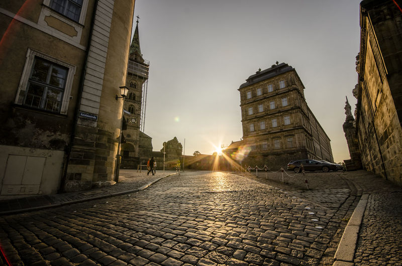 Architecture Bright Building Building Exterior Built Structure Car City Cobblestone Footpath Lens Flare Mode Of Transportation Motor Vehicle Nature No People Outdoors Paving Stone Sky Street Sun Sunbeam Sunlight Sunset Transportation