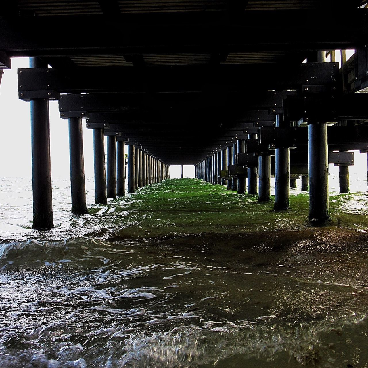 underneath, below, architectural column, connection, in a row, bridge - man made structure, architecture, water, pier, diminishing perspective, built structure, under, pillar, no people, day, sea, nature, outdoors