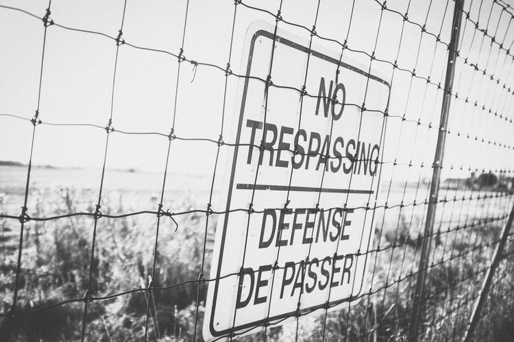 Warning sign by fence