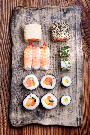 Sushi set on handmade pottery plate on wooden table from above Freshness Rustic Snack Sushi Sushitime Above Ceramic Delicious Directly Above Food Fresh Freshness Healthy Healthy Eating No People Overhead View Pottery Seafood Still Life Sushi Sushi Rolls Sushi Time Table Tasty Wooden