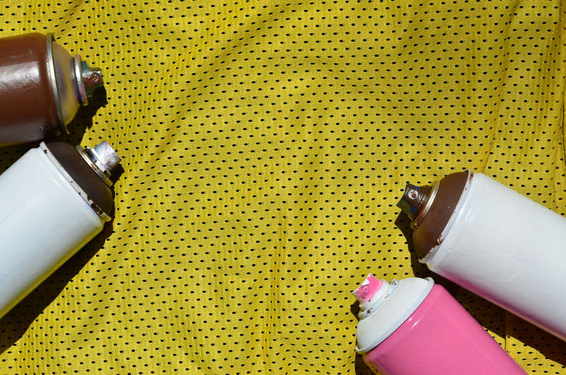 High angle view of spray cans on yellow fabric