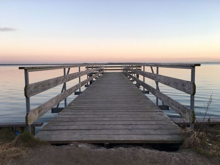 Wooden pier on sea during sunset