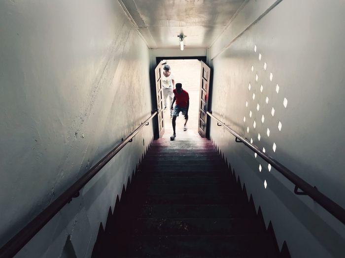 Rear view of people walking on illuminated tunnel