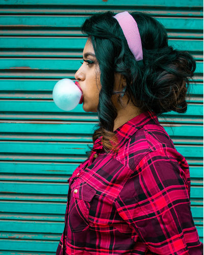 Side view of woman blowing bubble against wall
