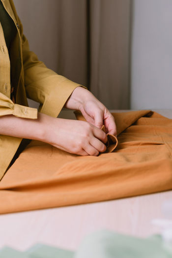Midsection of woman sitting on table at home
