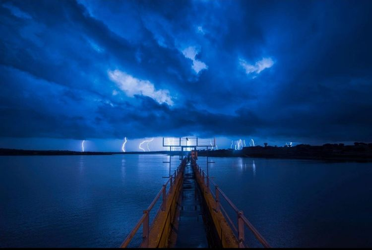 Scenic view of sea against cloudy sky at night