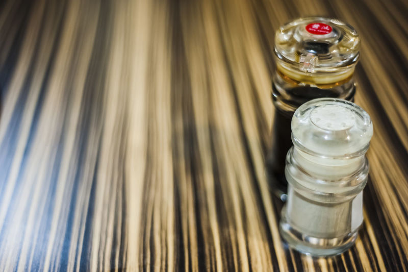High angle view of soy sauce with pepper shaker on table