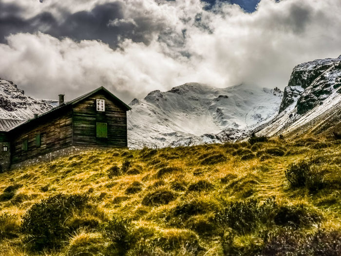 House on field by mountain against sky