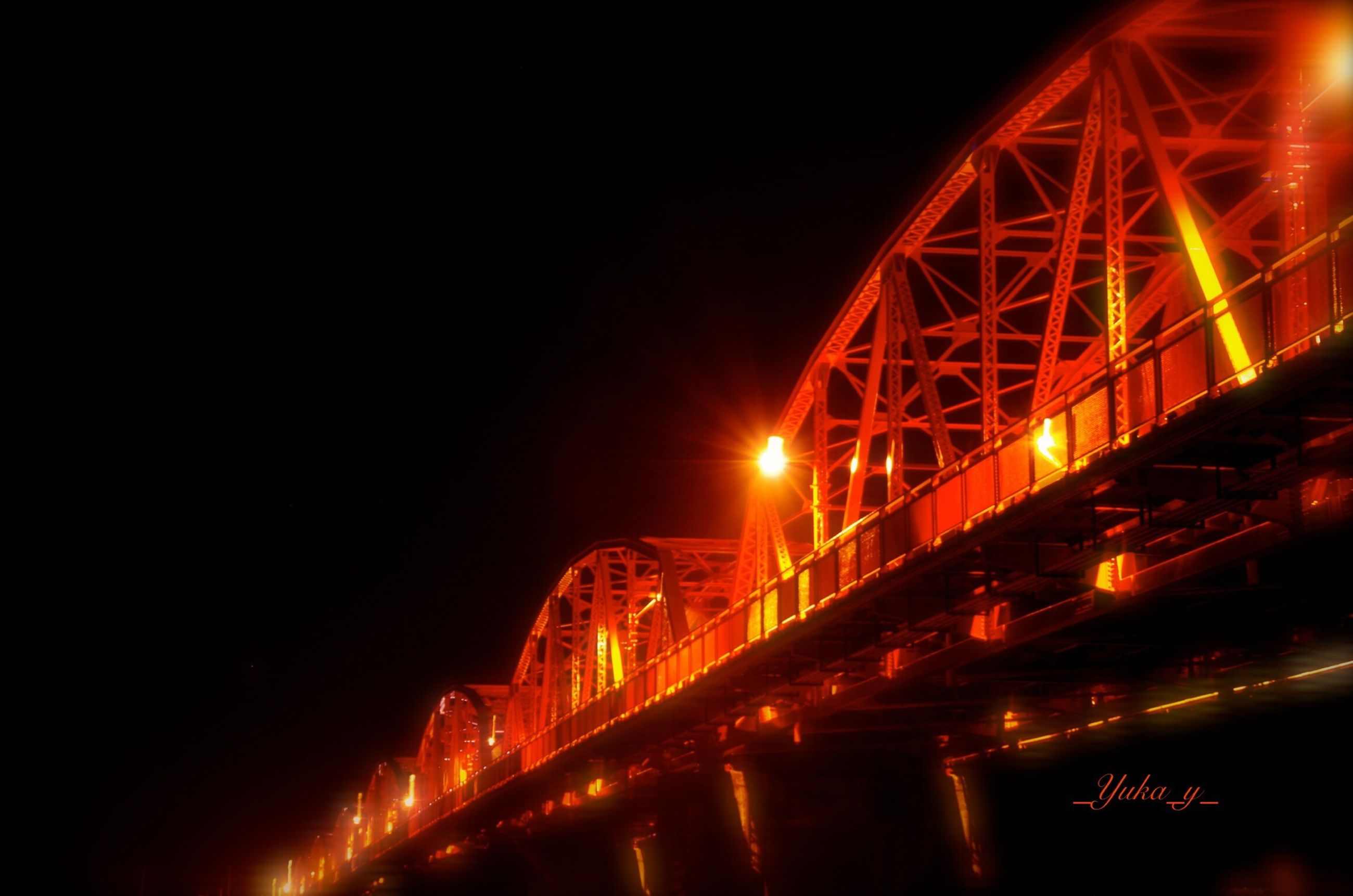 night, illuminated, built structure, architecture, low angle view, bridge - man made structure, connection, clear sky, copy space, engineering, transportation, city, lighting equipment, sky, light - natural phenomenon, building exterior, outdoors, street light, ferris wheel, travel destinations