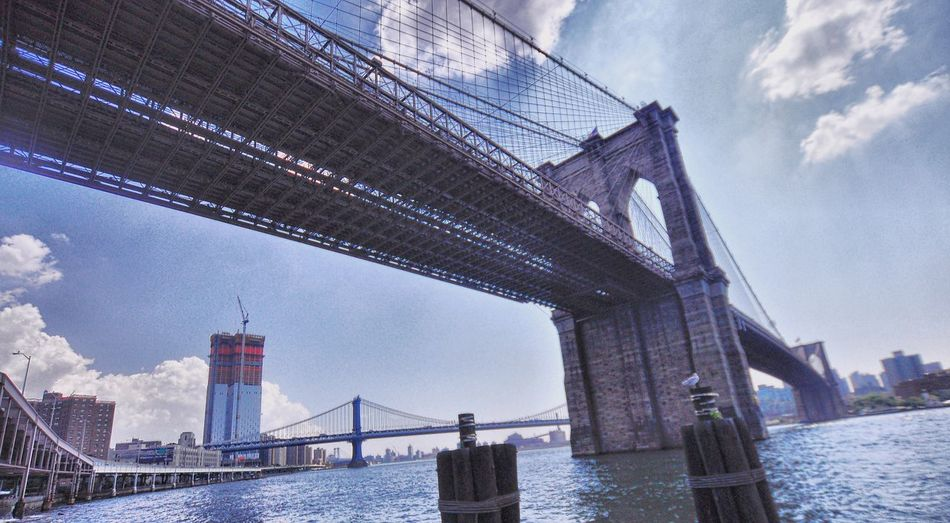 Bridge - Man Made Structure Connection Architecture Built Structure Engineering Sky Transportation NYC Cloud - Sky Water River City Bridge Day Low Angle View Outdoors No People Brooklyn Bridge / New York Manhattan Bridge East River, NYC Summer Midday Sunlight