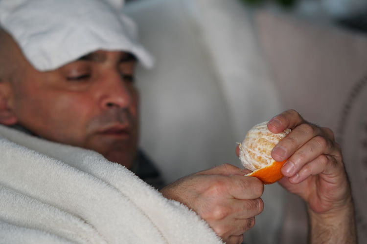Close-up of man having orange while lying on sofa