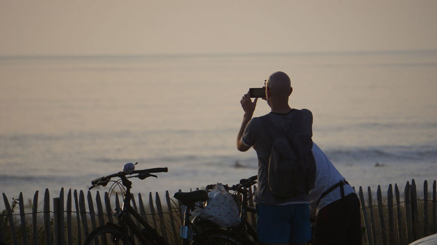 Rear view of man photographing sea with smart phone against sky