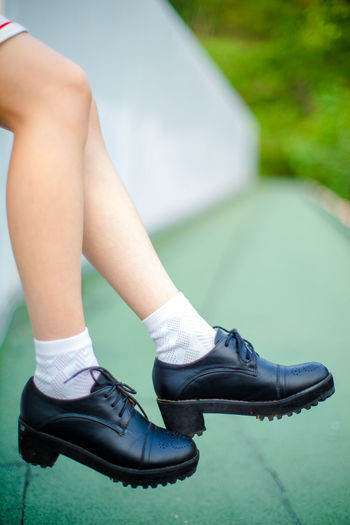 Low Section Of Girl Wearing Black Leather Shoes