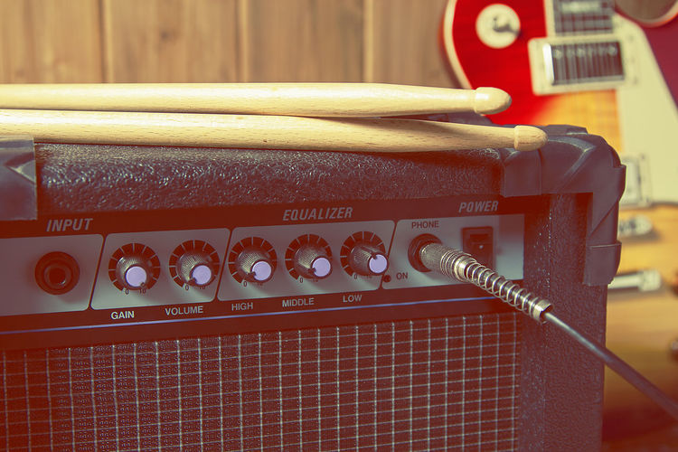 Close-up of drumsticks on amplifier