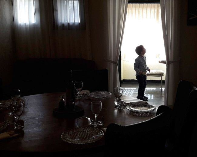 Man and woman standing by window at home