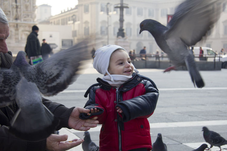 Smiling son looking at pigeons by father in city during winter