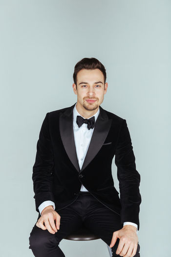 Portrait of confident young man in tuxedo sitting against blue background