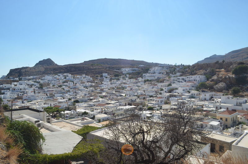 Lindos by mountains against clear blue sky