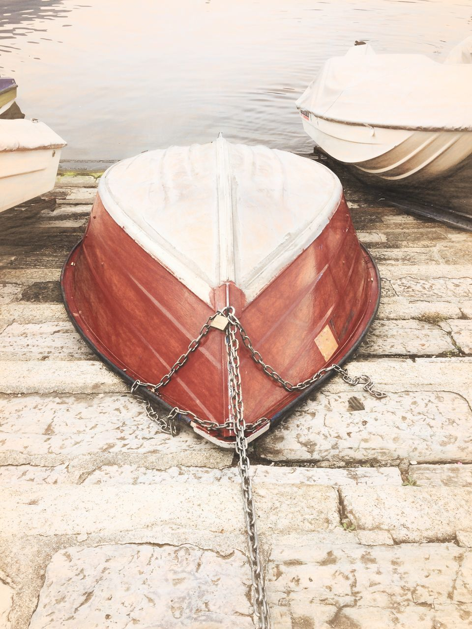 water, nautical vessel, transportation, mode of transportation, no people, day, moored, rope, nature, wood - material, high angle view, outdoors, lake, rowboat, architecture, red, sunlight, wall