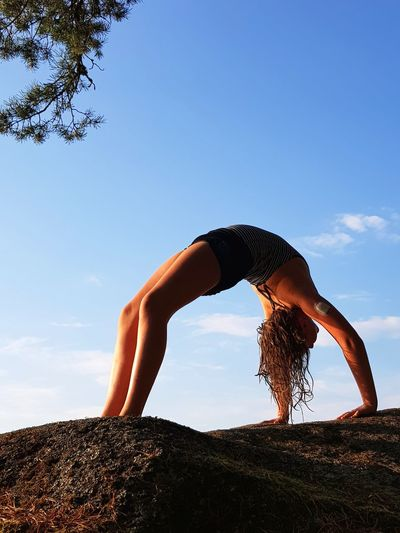 Low angle view of girl practicing yoga on rock against sky