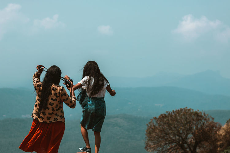 Rear View Of Female Friends Standing On Cliff Against Sky